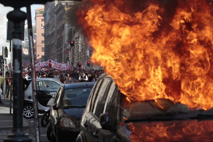 "A car is set on fire as protesters clash with police in Rome, Saturday, Oct. 15, 2011, as violence broke out during a demonstration, part of worldwide protests against corporate greed and austerity measures. The ""Occupy Wall Street"" protests, that began in Canada and spread to cities across the U.S., moved Saturday to Asia and Europe, linking up with anti-austerity demonstrations that have raged across the debt-ridden continent for months. (AP Photo/Gregorio Borgia)"