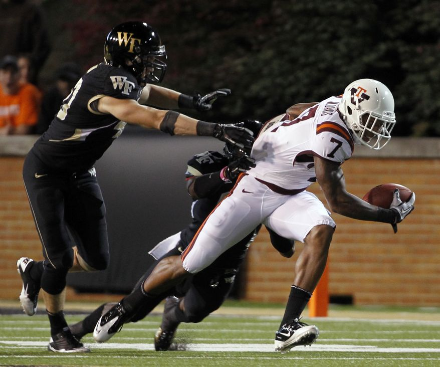 Virginia Tech's Marcus Davis (7) breaks free from Wake Forest's Joey Ehrmann, left, and Kenny Okoro, rear, during the second half  in Winston-Salem, N.C., on Saturday Oct. 15, 2011. Virginia Tech won 38-17. (AP Photo/Bob Leverone)