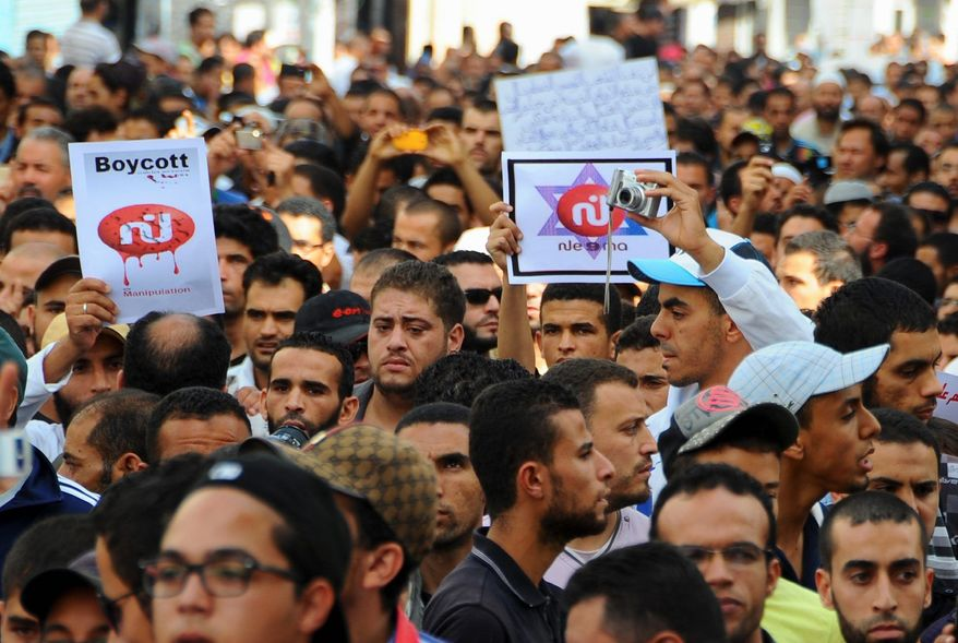 """Protesters, some holding a picture of a defaced logo of a television channel, crowd a street in Tunis, Tunisia, after Friday prayer. The protest was sparked by the airing on television of """"Persepolis,"""" an animated film that has offended ultraconservative Muslims. (Associated Press)"""