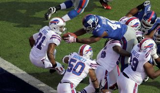 New York running back Ahmad Bradshaw dives past Buffalo safety Jairus Byrd to score one of his three touchdowns in the Giants' 27-24 victory. (Associated Press)