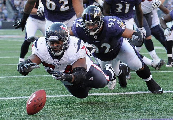 Houston guard Wade Smith (foreground) leaps toward a ball fumbled by the Texans in the end zone as Baltimore's Haloti Ngata (92) bears down. (Associated Press)