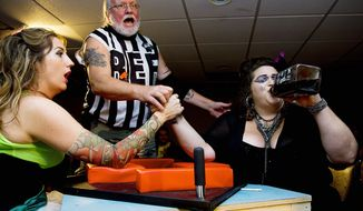"""Referee Philip Yunger reacts as """"Scarlett O'Scara,"""" aka Ann Marie Wilson (left) of Silver Spring, and """"Amy Smackhouse,"""" aka Andrea Kavanagh of the District, prepare to arm-wrestle during the D.C. Lady Arm Wrestlers league event. The arm-wrestling competitions raise money for charity. (Barbara L. Salisbury/The Washington Times)"""