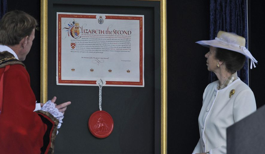 Britain's Princess Anne (right), with Councillor Paul Heaphy, mayor of the town of Royal Wootton Bassett, unveils the Letters Patent granting the English town royal status on Sunday, Oct. 16, 2011. (AP Photo/Ben Birchall/PA Wire)