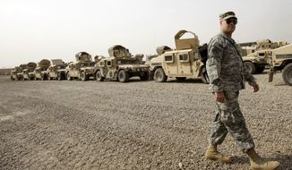On Saturday, Oct. 15, 2011, a U.S. Army soldier walks past military Humvees that are to be shipped out of Iraq from a staging yard at Camp Sather, part of the sprawling U.S. military's Victory Base Complex in Baghdad. (AP Photo/Khalid Mohammed) ** FILE **