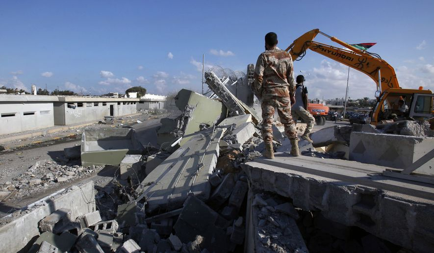 Libyan revolutionary fighters use heavy machinery to tear down a guard tower at Col. Moammar Gadhafi's Bab al-Aziziya compound in Tripoli, Libya, on Sunday, Oct. 16, 2011. (AP Photo/Abdel Magid al-Fergany)