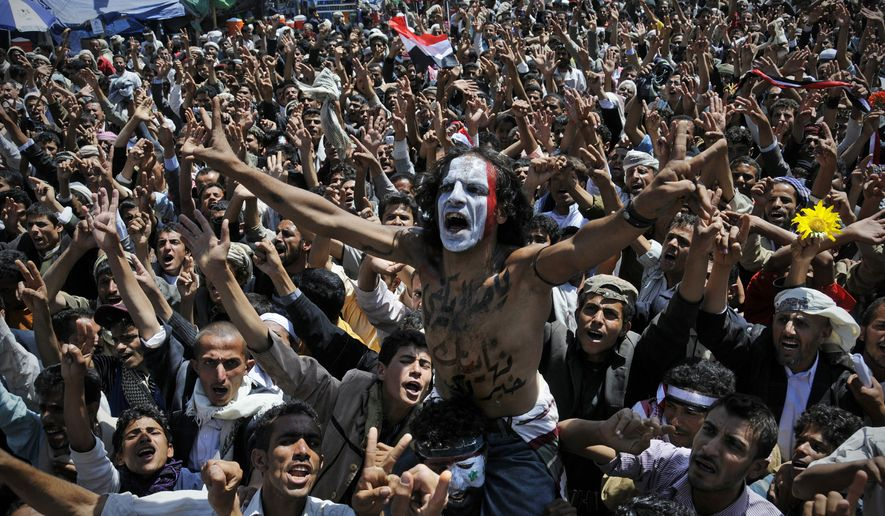 "A protester (center) with the colors of Yemen's national flag painted on his face and Arabic writing on his chest that translates as ""Saleh, you're better off leaving,"" chants slogans during a demonstration demanding the resignation of Yemeni President Ali Abdullah Saleh in Sanaa, Yemen, on Sunday, Oct. 16, 2011. (AP Photo/Mohammed Hamoud)"