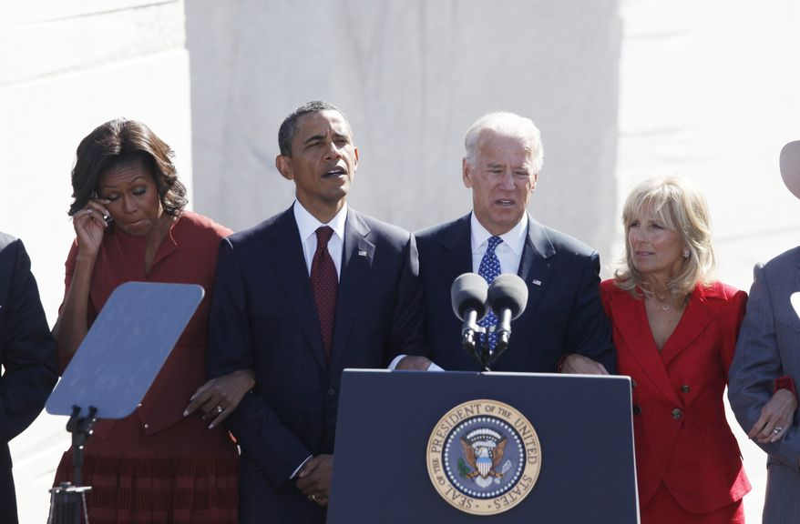 """President Obama (second from left), first lady Michelle Obama (left), Vice President Joseph R. Biden Jr. and Jill Biden, with arms locked, sing """"We Will Overcome"""" at the dedication of the Martin Luther King Jr. Memorial in Washington on Sunday, Oct. 16, 2011. (AP Photo/Charles Dharapak)"""