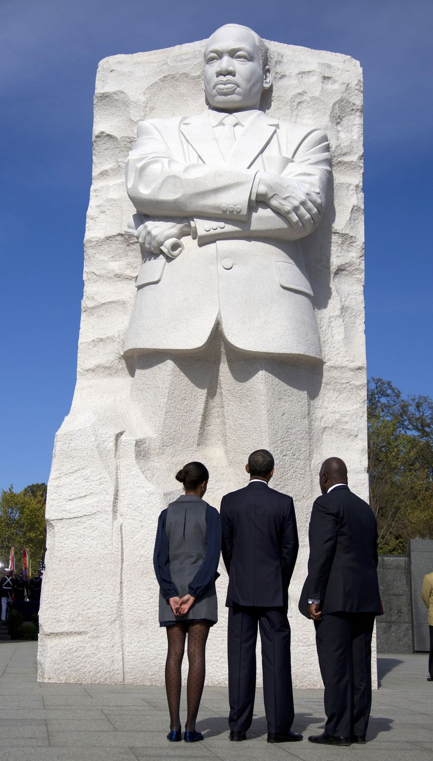 President Obama (center), his daughter Malia (left) and Harry Johnson, president and CEO of the Martin Luther King Jr. Memorial Foundation, look up at the Martin Luther King Jr. Memorial on Sunday, Oct. 16, 2011, on the National Mall in Washington. (AP Photo/Carolyn Kaster)