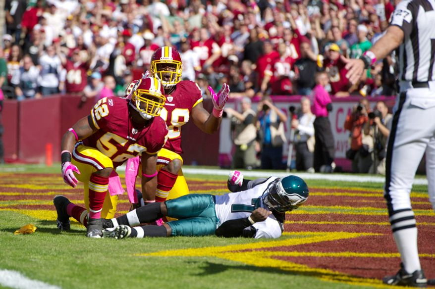 Brian Orakpo (98) and Rocky McIntosh (52) of the Washington Redskins react after what they thought was a safety on Philadelphia Eagles quarterback Michael Vick (7) was called as roughing the passer on McIntosh during the first quarter at FedEx Field. (Andrew Harnik / The Washington Times)