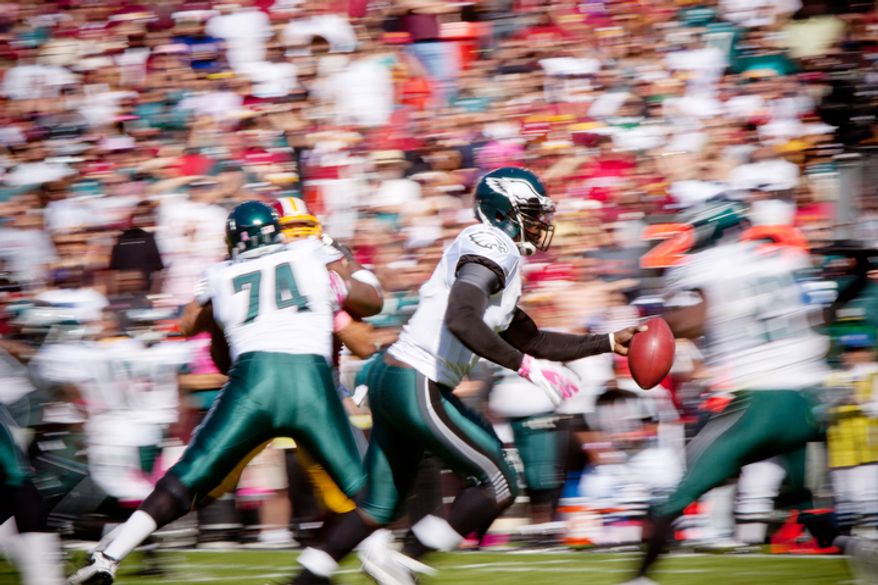 The Washington Redskins watch as Philadelphia Eagles Michael Vick (7) hands off the ball during the first quarter. (Pratik Shah / The Washington Times)