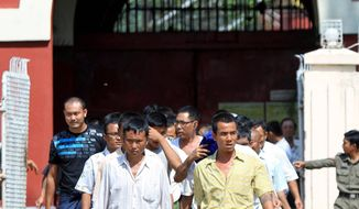 Prisoners walk out of Insein Prison  in Yangon, Myanmar, on Wednesday. The government has begun releasing prisoners but has held back on freeing some prominent political figures. (Associated Press)