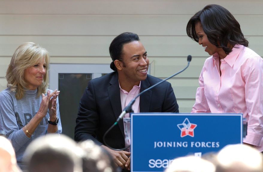 First lady Michelle Obama greets Army Sgt. Johnny Agbi with Jill Biden during a Joining Forces initiative event Monday in Washington. Sears, Rebuilding Together and volunteers will complete the retrofit on Sgt. Agbi's home to make it wheelchair accessible. Sgt. Agbi was injured while serving in Afghanistan. (Associated Press)