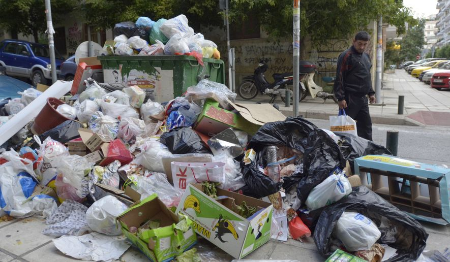 A pedestrian walks past a pile of garbage in the northern port of Thessaloniki, Greece, the country's second-largest city, on Sunday, Oct. 16, 2011. (AP Photo/Nikolas Giakoumidis)