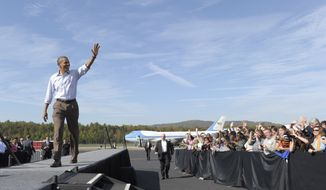 President Obama greets the crowd upon his arrival at Asheville Regional Airport in Fletcher, N.C., on Monday, Oct. 17, 2011, to begin his three-day bus tour promoting the American Jobs Act. (AP Photo/Susan Walsh)