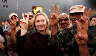 Secretary of State Hillary Rodham Clinton and Libyan freedom fighters signal victory before her departure from Tripoli on Tuesday. (Associated Press)