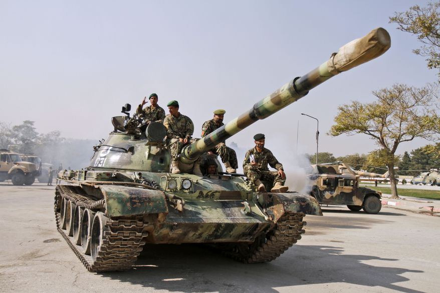 Afghan national army soldiers sit atop an armored vehicle at the Defense Ministry in Kabul, Afghanistan, on Oct. 18, 2011. (Associated Press)