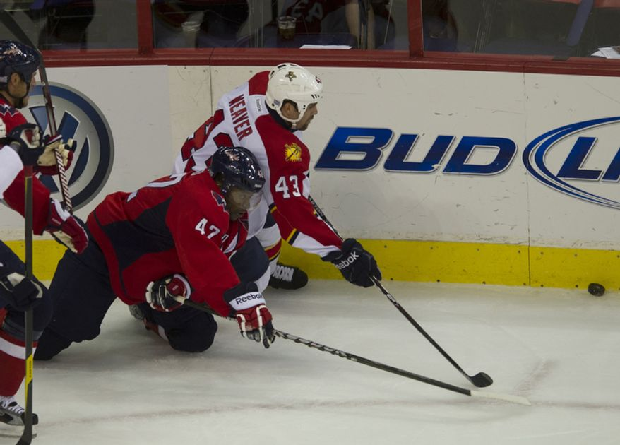Joel ward (42) of the Washington Capitals reaches for the puck against Mike Weaver (43) of the Florida Panthers in the first period as the Capitals host the Panthers at the Verizon Center in Washington,D.C., Tuesday, October 18, 2011. (Rod Lamkey Jr/The Washington Times)