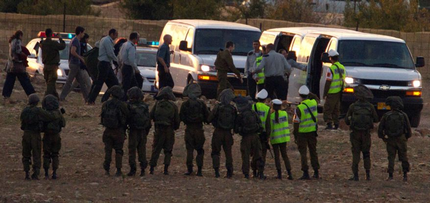 Released Israeli soldier Gilad Schalit , center, walks to a car after landing in Mitzpe Hila, northern Israel,Tuesday, Oct. 18, 2011. Looking thin, weary and dazed, an Israeli soldier returned home Tuesday from more than five years of captivity in the Gaza Strip in exchange for hundreds of Palestinian prisoners whose joyful families greeted them with massive celebrations. (AP Photo/Ariel Schalit)