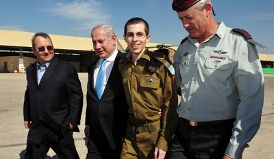 Released Israeli soldier Gilad Schalit (second from right) walks with Israeli Prime Minister Benjamin Netanyahu (second from left), Defense Minister Ehud Barak (left) and Israeli Chief of Staff Lt. Gen. Benny Gantz at the Tel Nof Air Base in southern Israel on Tuesday, Oct. 18, 2011. (AP Photo/Israeli Defense Ministry)