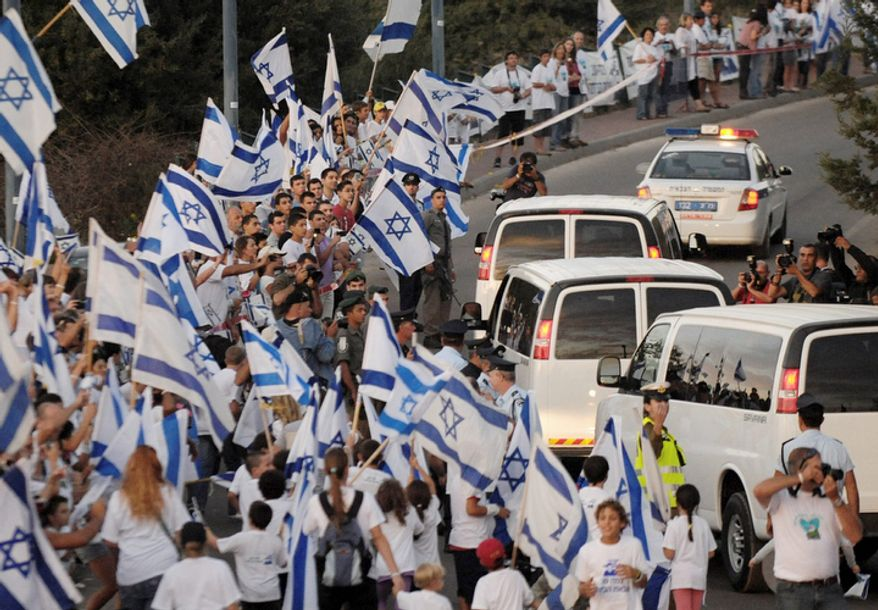 Flag-waving Israelis greet the convoy carrying freed Israeli soldier Gilad Schalit making its way to his home in Mitzpe Hila, northern Israel, Tuesday, Oct. 18, 2011.  (AP Photo/Moran Maayan)