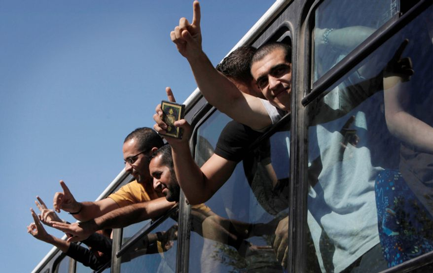 """Freed Palestinian prisoners from Israeli jails flash """"V"""" signs as they bear from their bus while they leave the Egyptian terminal of the Gaza Egypt border crossing of Rafah, Egypt Tuesday, Oct. 18, 2011.  (AP Photo/Nasser Nasser)"""