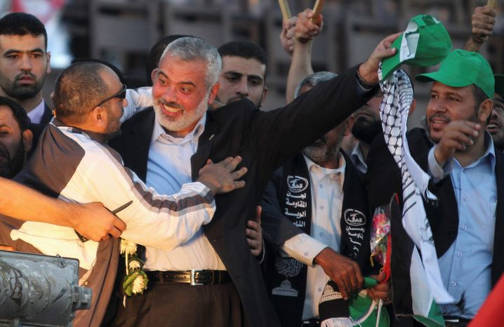 Freed Palestinian prisoner Palestinian Khalil Abu Alba who deliberately drove a bus into a crowd of Israelis killing 8 people, is greeted by Gaza's Hamas Prime Minister Ismail Haniyeh during a rally celebrating the release of Palestinian prisoners in Gaza City, Tuesday, Oct. 18, 2011. (AP Photo/Hatem Moussa)