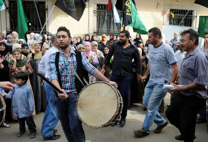 Palestinians dance and wave various flags, at the Bourj al-Barajneh Palestinian refugee camp, in Beirut, Lebanon, Tuesday Oct. 18, 2011.  The group gathered to celebrate the release of hundreds of Palestinian detainees from Israeli jails in a prisoners exchange with Israeli soldier Gilad Schalit,  between the Palestinian militant group Hamas and Israel. ( AP Photo/Ahmad Omar)