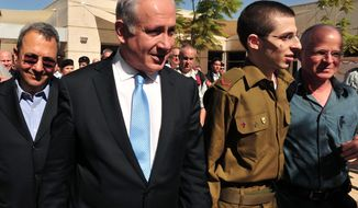 Released Sgt. Gilad Schalit (second from right) walks with his father, Noam (right), Israeli Prime Minister Benjamin Netanyahu (second from left) and Israeli Defense Minister Ehud Barak (left) at the Tel Nof Air Base in southern Israel on Oct. 18, 2011. (AP Photo/Israeli Defense Ministry)
