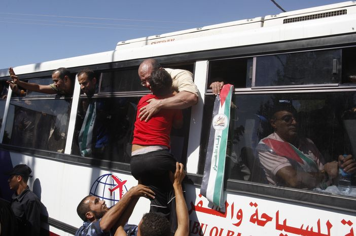 A child hugs a released Palestinian prisoner at the Rafah border crossing between Egypt and the Gaza Strip on Tuesday, Oct. 18, 2011. (AP Photo/Hatem Moussa)