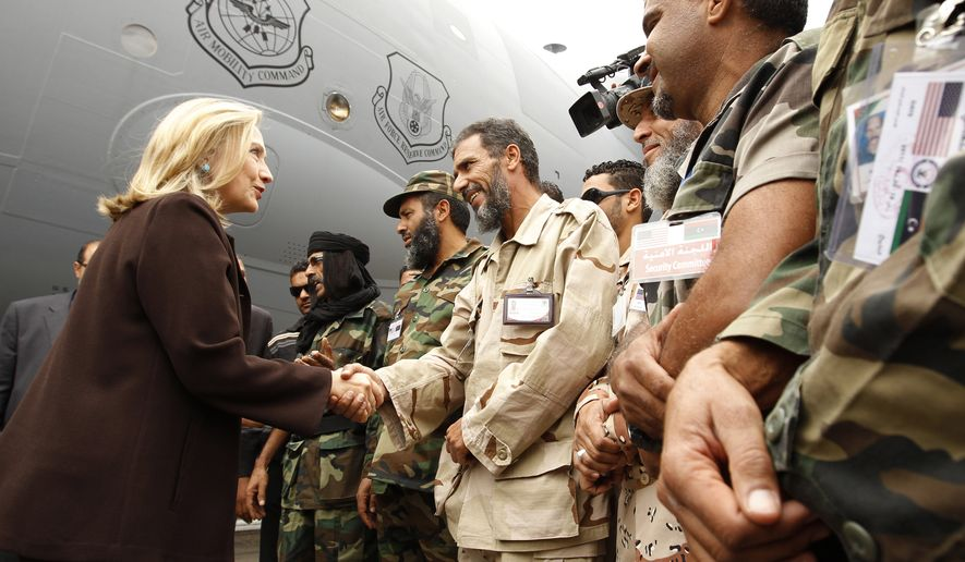 U.S. Secretary of State Hillary Rodham Clinton meets Libyan revolutionary soldiers at the steps of her C-17 military transport upon her arrival in Tripoli, Libya, on Tuesday, Oct. 18, 2011. The Obama administration announced increased U.S. aid for Libya, including medical care for wounded fighters and additional assistance to secure weaponry that many fear could fall into the hands of terrorists. (AP Photo/Kevin Lamarque, Pool)