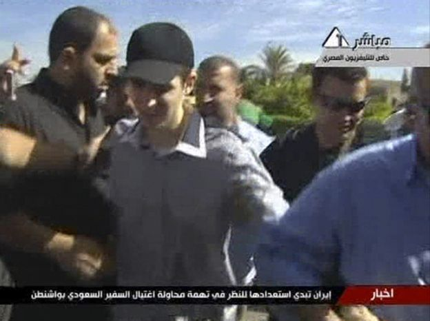 In this image from Egypt TV on Tuesday, Oct. 18, 2011, Israeli soldier Gilad Schalit is seen at an undisclosed location in the Gaza-Egypt border area accompanied by Hamas guards as he is moved into Egypt from captivity in Gaza, beginning an elaborate prisoner swap deal in which hundreds of Palestinian inmates are to be freed in return for the captured tank crewman. (AP Photo/ Egypt TV)