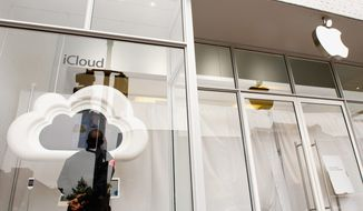 A security guard for the Apple store in Georgetown stands in the window while that store and all others worldwide close for three hours Wednesday to allow employees to watch a webcast memorial service for co-founder Steve Jobs. (Andrew Harnik/The Washington Times)