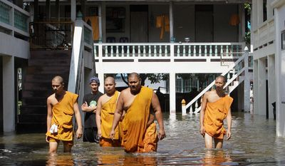 Thai Buddhist monks wade through Ban Kadee temple in Pathum Thani province, north of Bangkok, on Wednesday. Thai authorities were staging a fighting retreat Wednesday against floodwaters that threaten Bangkok after the country's oldest factory park was completely inundated and another one faced imminent threat.