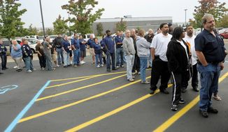 Members and leaders of the United Auto Workers line up to vote on their new contract last week at the Region 1 UAW headquarters in Warren, Mich. The labor deals are the first since the taxpayer bailouts approved by President Obama for GM and Chrysler in 2009. (Associated Press)