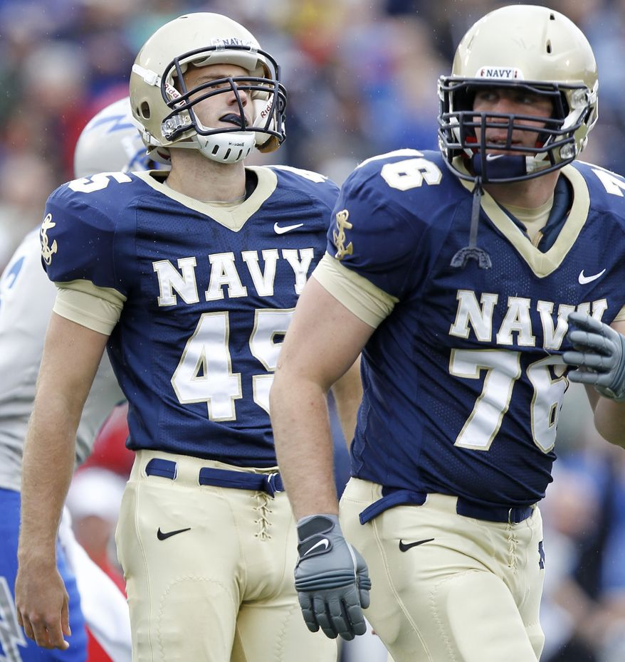 Navy kicker Jon Teague (45) reacts after missing an extra point during overtime against Air Force as offensive tackle David Sumrall (76) looks on. The Mids have had four kicks blocked this season, the latest a 41-yarder against Rutgers last Saturday.. (AP Photo/Luis M. Alvarez)
