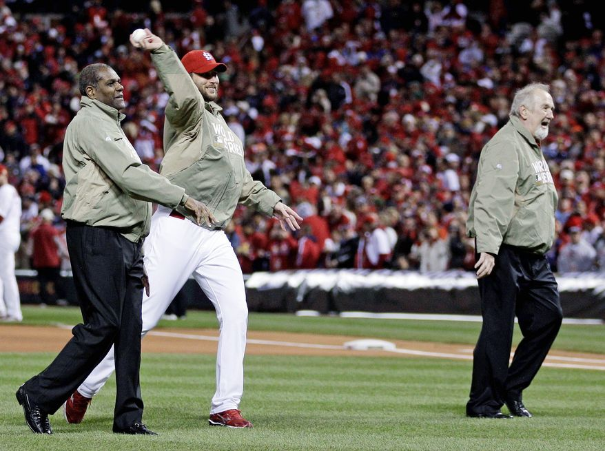 Former Cardinals greats Bob Gibson (left) and Bruce Sutter (right) flank Adam Wainwright as they throw out the ceremonial first pitch before Game 1 of the World Series on Wednesday night. (Associated Press)