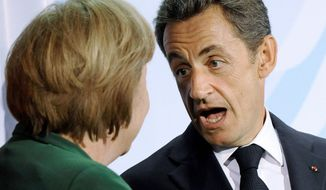 French President Nicolas Sarkozy talks with German Chancellor Angela Merkel in Berlin on Thursday after a meeting on the financial crisis. Europe's efforts to solve its debt crisis plunged into disarray after Germany and France could not bridge their differences in time for a summit Sunday. (Associated Press)