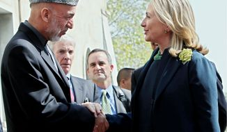 Secretary of State Hillary Rodham Clinton is greeted by Afghanistan President Hamid Karzai in Kabul on Thursday. She stressed the U.S. commitment to the Afghan peace process. (Associated Press)