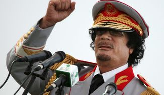 ** FILE ** Libyan dictator Moammar Gadhafi gestures during a 2010 ceremony to mark the 40th anniversary of the evacuation of American military base personnel from Libya.