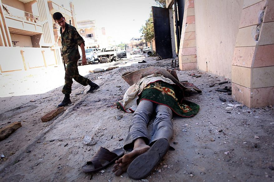 A revolutionary fighter walks by the body of a suspected Gadhafi loyalist in Sirte, Libya, on Oct. 20, 2011. (Associated Press)
