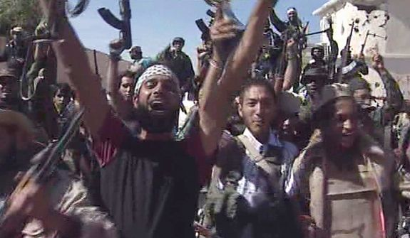 In this image taken from television on Oct. 20, 2011, Libyan fighters celebrate in the streets of Sirte after overrunning the remaining positions of Moammar Gadhafi loyalists in his hometown of Sirte, ending the last major resistance by former regime supporters still holding out two months after the fall of the capital Tripoli. (Associated Press/APTN)