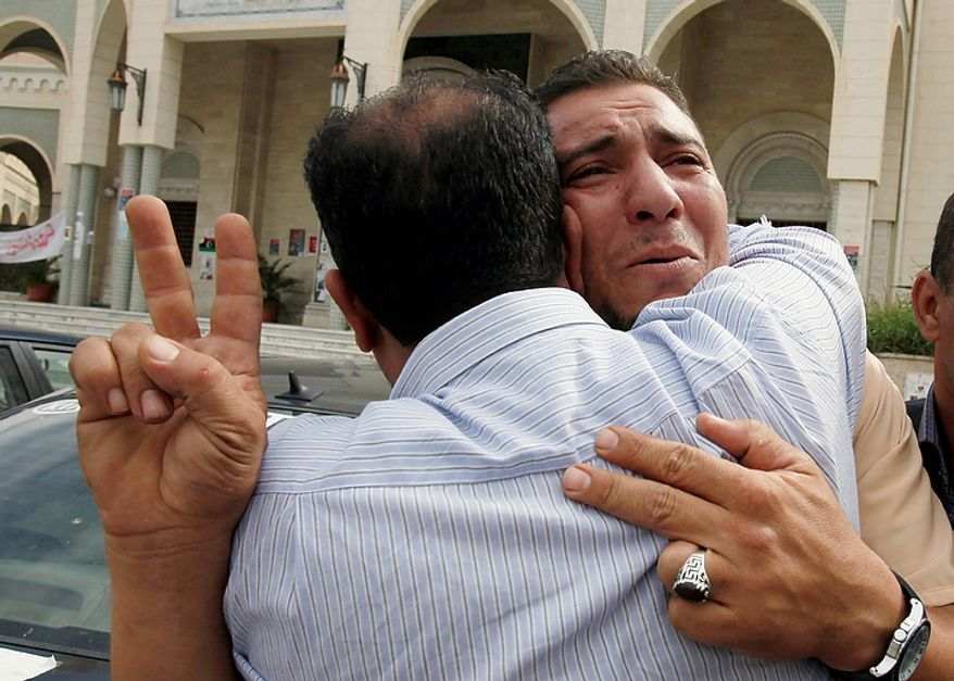 Libyans react to Col. Moammar Gadhafi's death in Tripoli, Libya, on Oct. 20, 2011. Libya's information minister said Gadhafi was killed Thursday when revolutionary forces overwhelmed his hometown, Sirte, the last major bastion of resistance two months after the regime fell. (Associated Press)