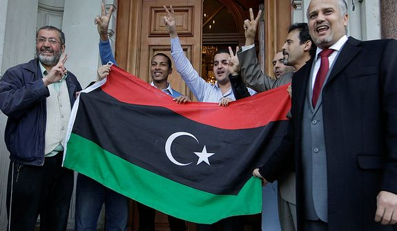 Staffers at the Libyan Embassy in London react to the death of Col. Moammar Gadhafi on Oct. 20, 2011. (Associated Press)