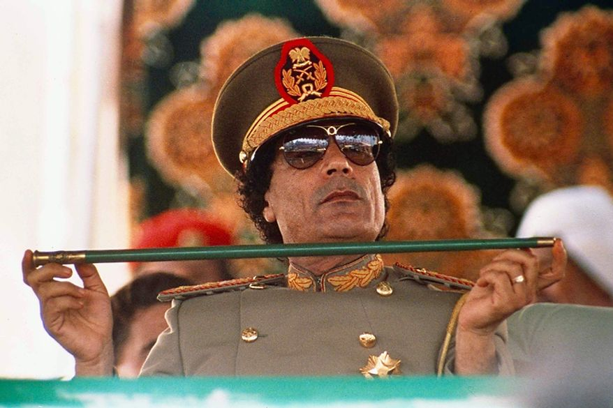 Libyan leader Col. Moammar Gadhafi holds a baton on Sept. 1, 1987, as he sits to review Libyan troops during the 18th anniversary celebration of Libya's revolution in Tripoli. (Associated Press)