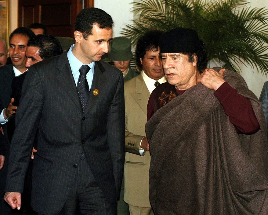 In this photo from March 22, 2005, Syrian President Bashar Assad (left) talks to Libyan leader Moammar Gadhafi prior the 17th League of Arab States' summit in Algiers, Algeria. (Associated Press)