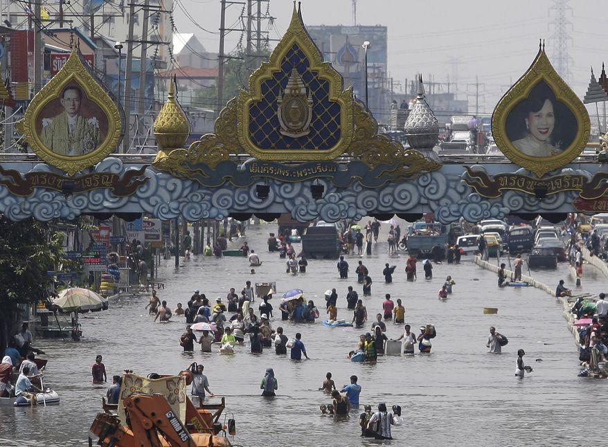Residents wade through floods in Rangsit district on the outskirts of Bangkok on Oct. 21, 2011. (Associated Press)