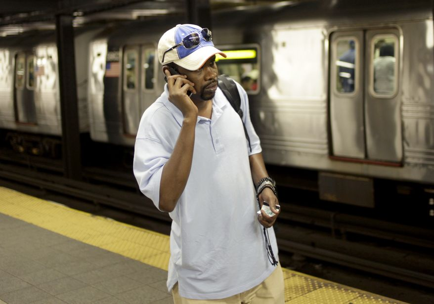 ** FILE ** In this Sept. 27, 2011, photo, Mory Bailo Aw makes a cellphone call from a subway platform to get some last-minute directions to a friends house in New York. (AP Photo/Seth Wenig, File)