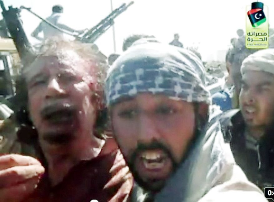 THE END IS NIGH: This image taken from Libyan TV purports to show Moammar Gadhafi alive and surrounded by revolutionary fighters on Thursday. It shows a wounded Col. Gadhafi with a blood-soaked shirt and bloodied face. (Associated Press)