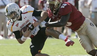 Maryland quarterback C.J. Brown is stopped short of first down yardage by Florida State's Nigel Bradham in the first quarter. Brown left the game after a helmet-to-helmet hit. (AP Photo/Steve Cannon)