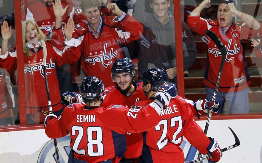 Washington Capitals center Marcus Johansson  celebrates with teammates Alexander Semin (28) of Russia and Mike Knuble after scoring on Detroit Red Wings goalie Ty Conklin during the first period of an NHL hockey game Saturday, Oct. 22, 2011, in Washington. (AP Photo/Ann Heisenfelt)